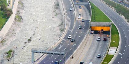 La autopista generando un farellon de cemento contra el río.